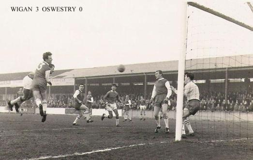 Harry Lyon latches on to a Walter Stanley (third from right) cross. Carl Davenport lurks for any rebounds.  Photo courtesy of WiganWorld.