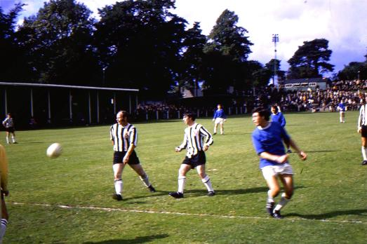 Geoff Davies attacks as ex-Latics player Alf Craig (left) looks on. Kenny Morris and Doug Coutts watch from defence and Bobby Todd from midfield.